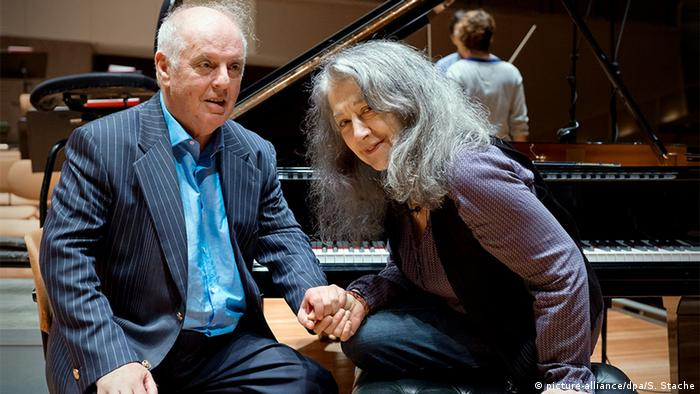 Daniel Barenboim and Martha Argerich holding hands while seated at the piano