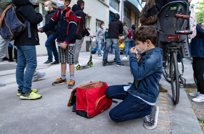 A boy adjusts his mask before entering his primary school in Paris on April 26, 2021.