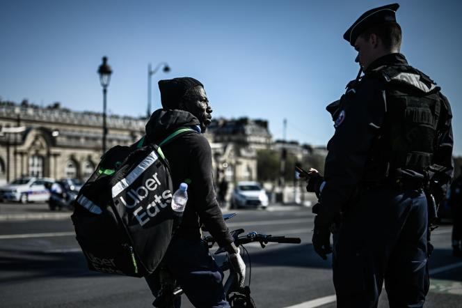 A police officer controls an Uber Eats delivery man, during the French containment of March 2020, in Paris.