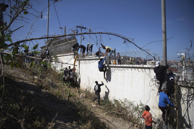 People climb a barbed wire wall in the border area between Morocco and Spain on May 18, 2021.