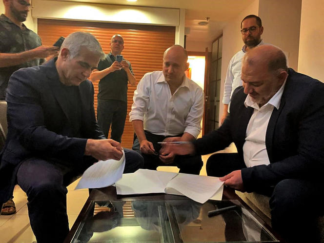 Mansour Abbas (right), leader of the conservative Islamic party, signs a coalition agreement with Israeli opposition leader Yaïr Lapid (left) and far-right leader Naftali Bennett (center) in Ramat Gan, near Tel Aviv, June 2, 2021. Photo provided by the United Arab List.