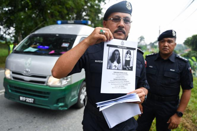 A Royal Malaysian Police officer shows a wanted poster with the portrait of missing 15-year-old Franco-Irish girl Nora Quoirin on August 9, 2019.