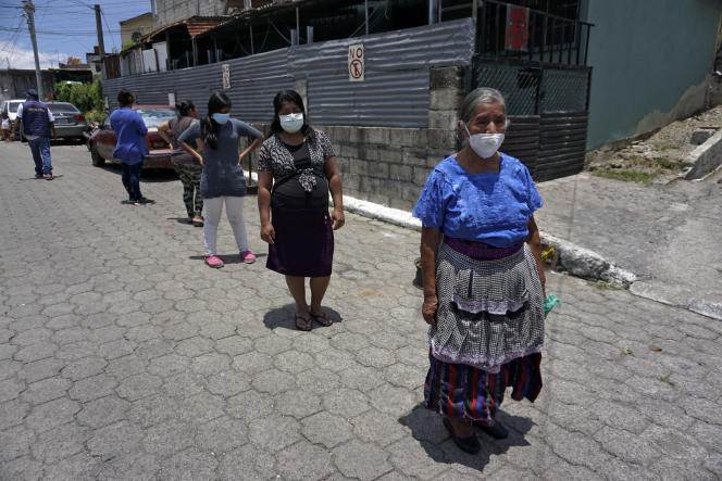 Women financially affected by the pandemic line up for a hot meal on July 24, 2020 in Guatemala.